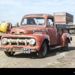 Rough Rusty Old Vintage Classic Ford Pickup Truck Driving Through A Farm With Discarded Equipment Tatty Country Appearance Distressed Appearance Stock Photo Alamy