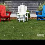 Red White And Blue Wooden Adirondack Chairs On A Green Lawn