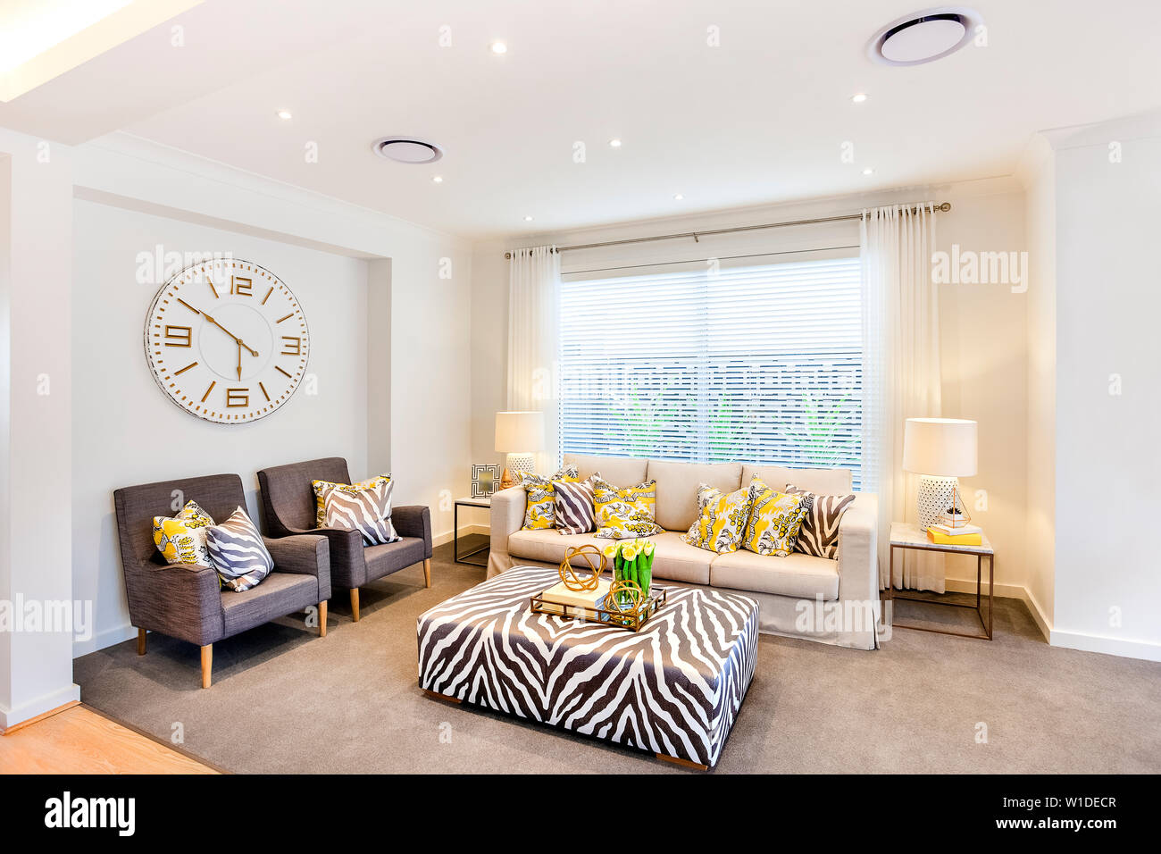 Living Room With A Stylish Sofa Set And A Quirky Center Table With Grey Carpeting And Wall Clock Behind The Sofa Chairs Stock Photo Alamy