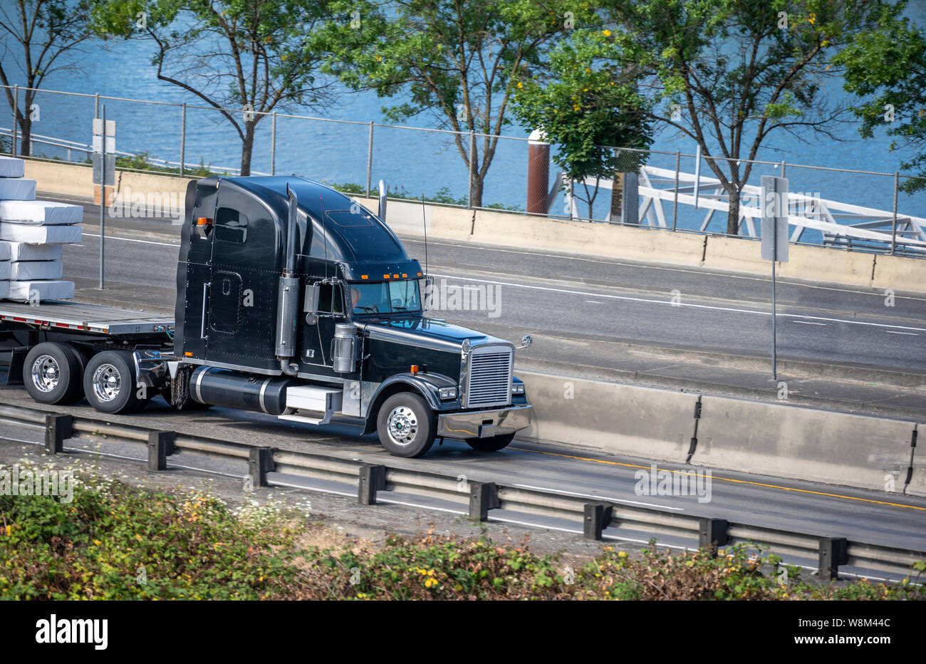 https www alamy com black big rig american bonnet semi truck with high exhaust pipes transporting stacked covered commercial cargo on flat bed semi trailer driving on the image263515068 html
