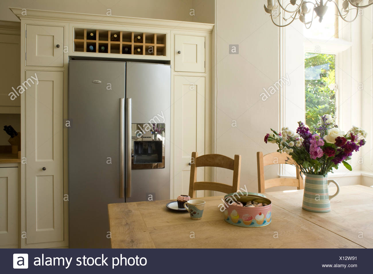 https www alamy com vase of summer flowers on table in country kitchen with wine storage above american style fridge freezer image276044301 html