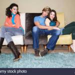 Third Wheel Sitting Arms Crossed On Opposite End Of Sofa Of Hugging Couple Stock Photo Alamy