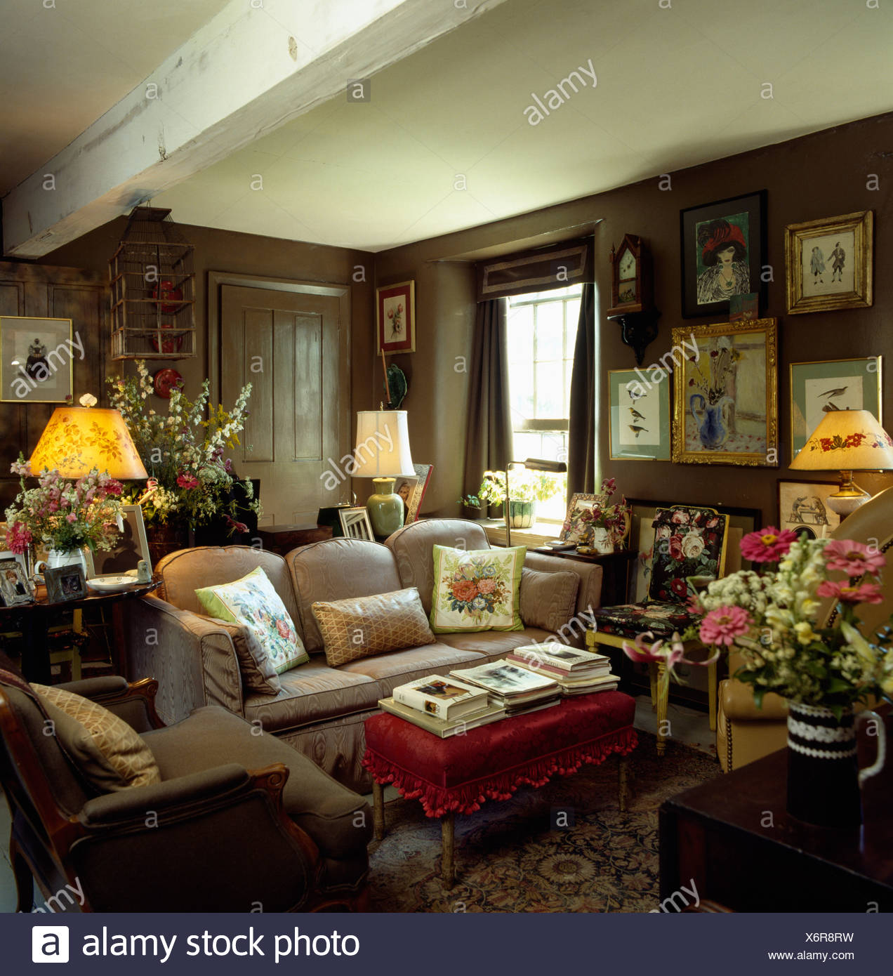 https www alamy com lighted lamps and pictures on walls of brown country livingroom with low ceiling and comfortable furniture image279565661 html