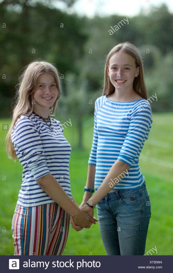 Teenage girls holding hands smiling portrait Stock Photo ...