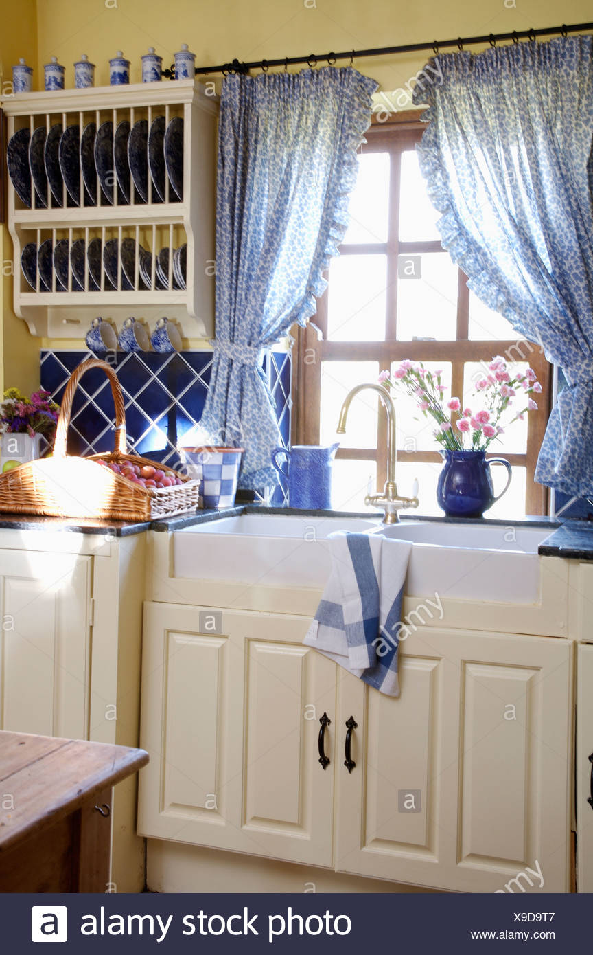 Blue Curtains On Window Above Double Belfast Sinks In Country Kitchen With Wall Mounted Plate Rack Above Worktop With Basket Stock Photo Alamy