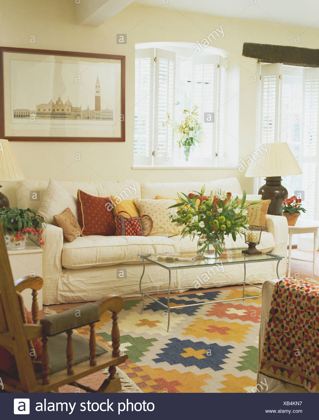 White Plantation Shutters On Window Above Cream Sofa In