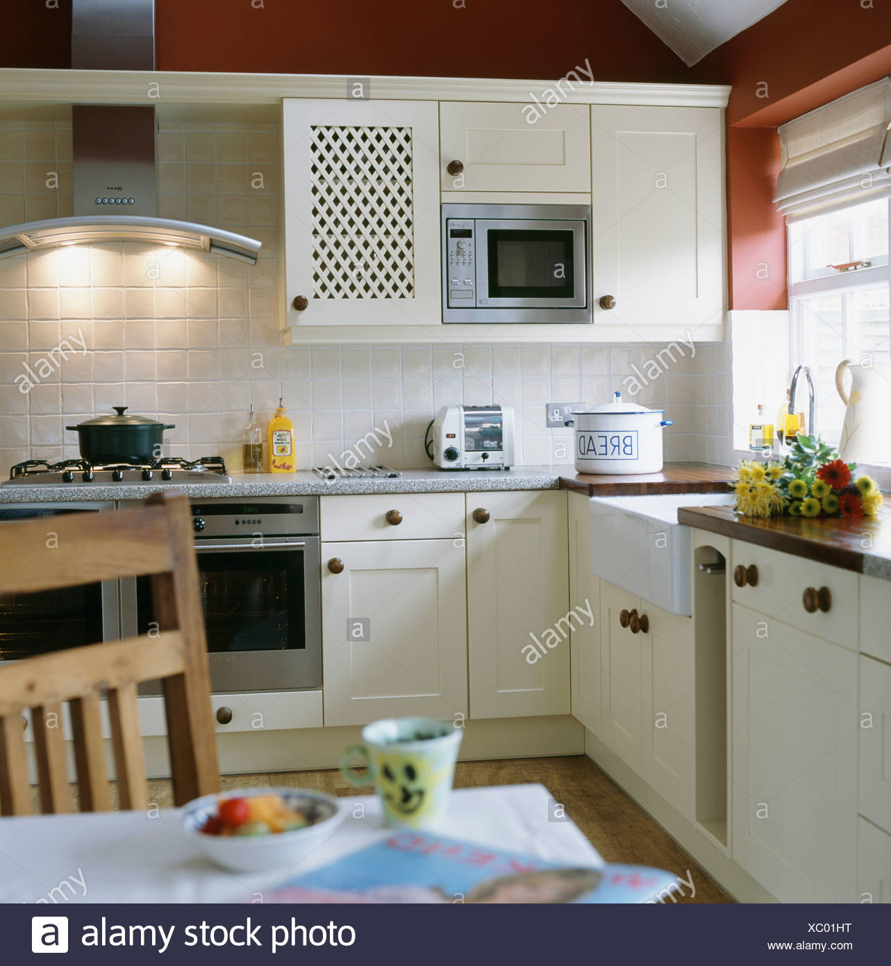 https www alamy com microwave oven fitted in wall cupboard in white cottage kitchen dining room with lighted extractor fan above range oven image282743044 html
