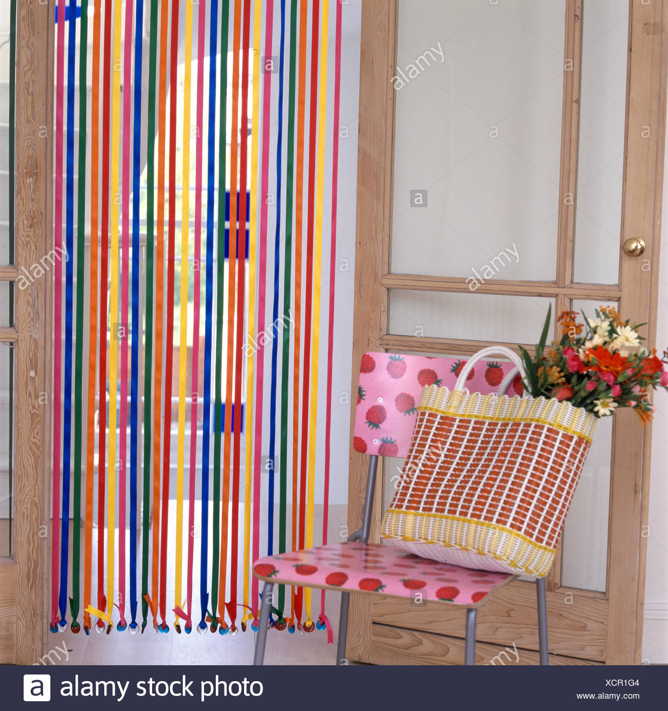 https www alamy com shopping bag on modern plastic chair in front of ribbon and bead curtain image283247892 html