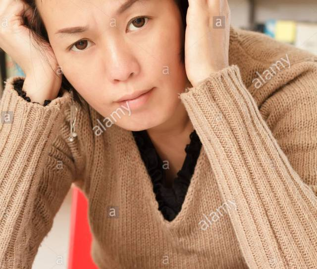 Worried Mature Asian Woman Sitting And Looking At You