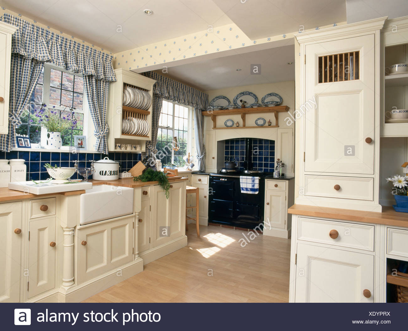 Blue Checked Curtains On Window In Country Kitchen With Fitted Cream Units And Black Range Oven Stock Photo Alamy