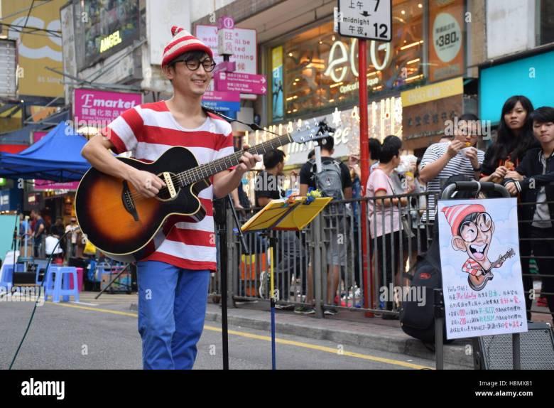 hongkong, china - junge asiaten gitarre spielen und singen auf der