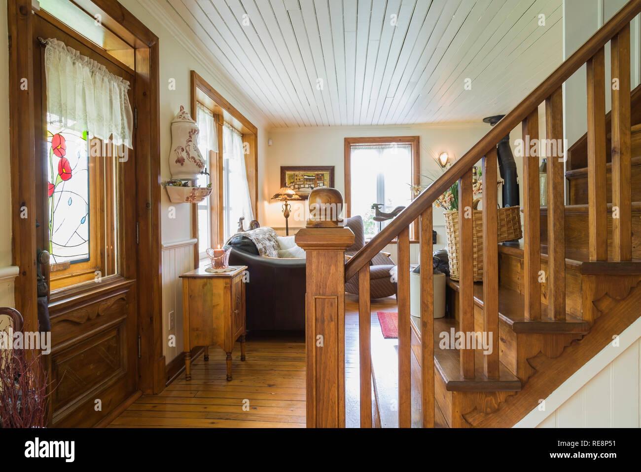 braun gebeiztem kiefernholz treppen zwischen esszimmer und wohnzimmer in einem alten 1892 canadiana cottage style home