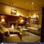 Gemutliches Wohnzimmer Mit Brennenden Lampen Und Beigefarbenen Sofas Am Kamin Stockfotografie Alamy