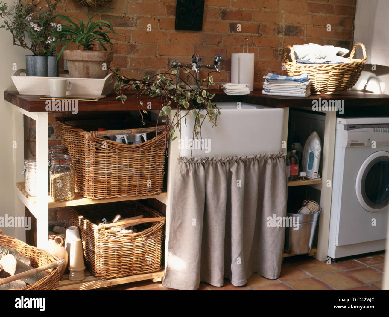 https www alamyimages fr photo image des paniers de rangement sur l etagere a cote de belfast lavabo dans l unite avec rideau gris rustique de pays dans la buanderie 54153748 html