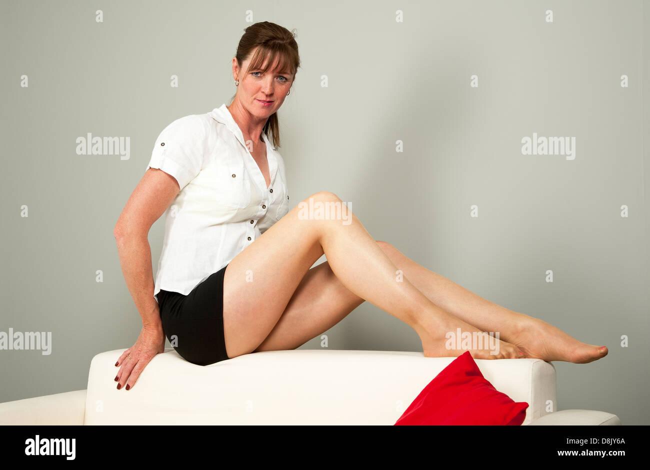 femme avec de longues jambes assis sur le dos d un canape blanc