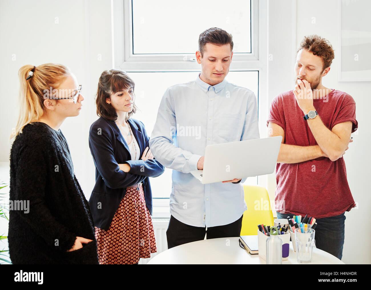 https www alamyimages fr photo image quatre personnes autour d une table a une reunion d affaires a la recherche d un ecran d ordinateur portable 123405907 html