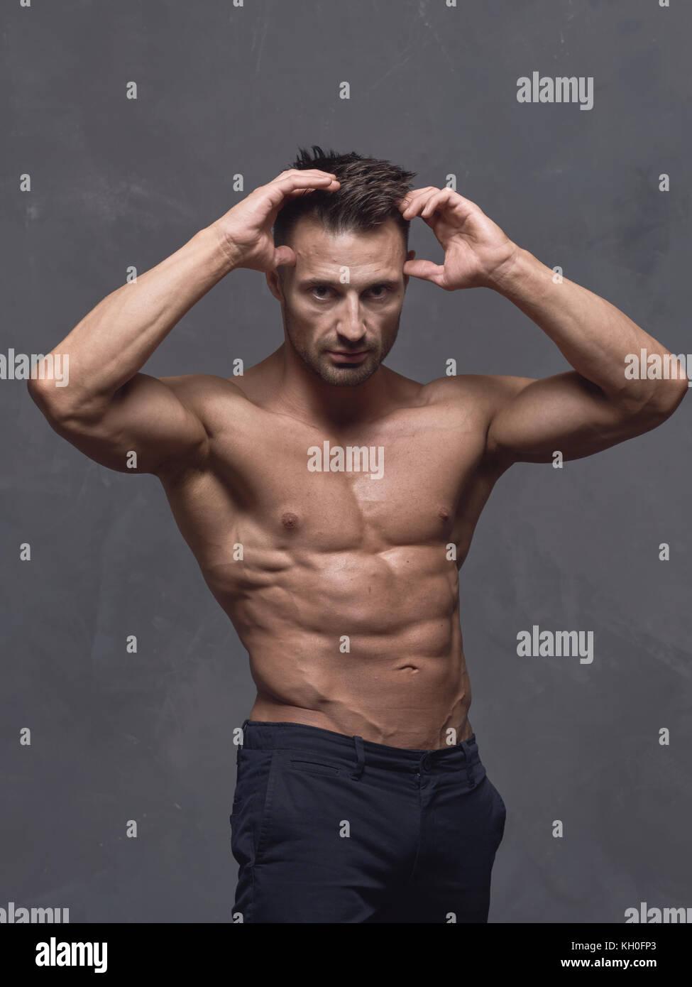 un homme aux cheveux noir avec une coupe courte est debout pres du mur texture gris le gars a strong muscle les bras et les epaules
