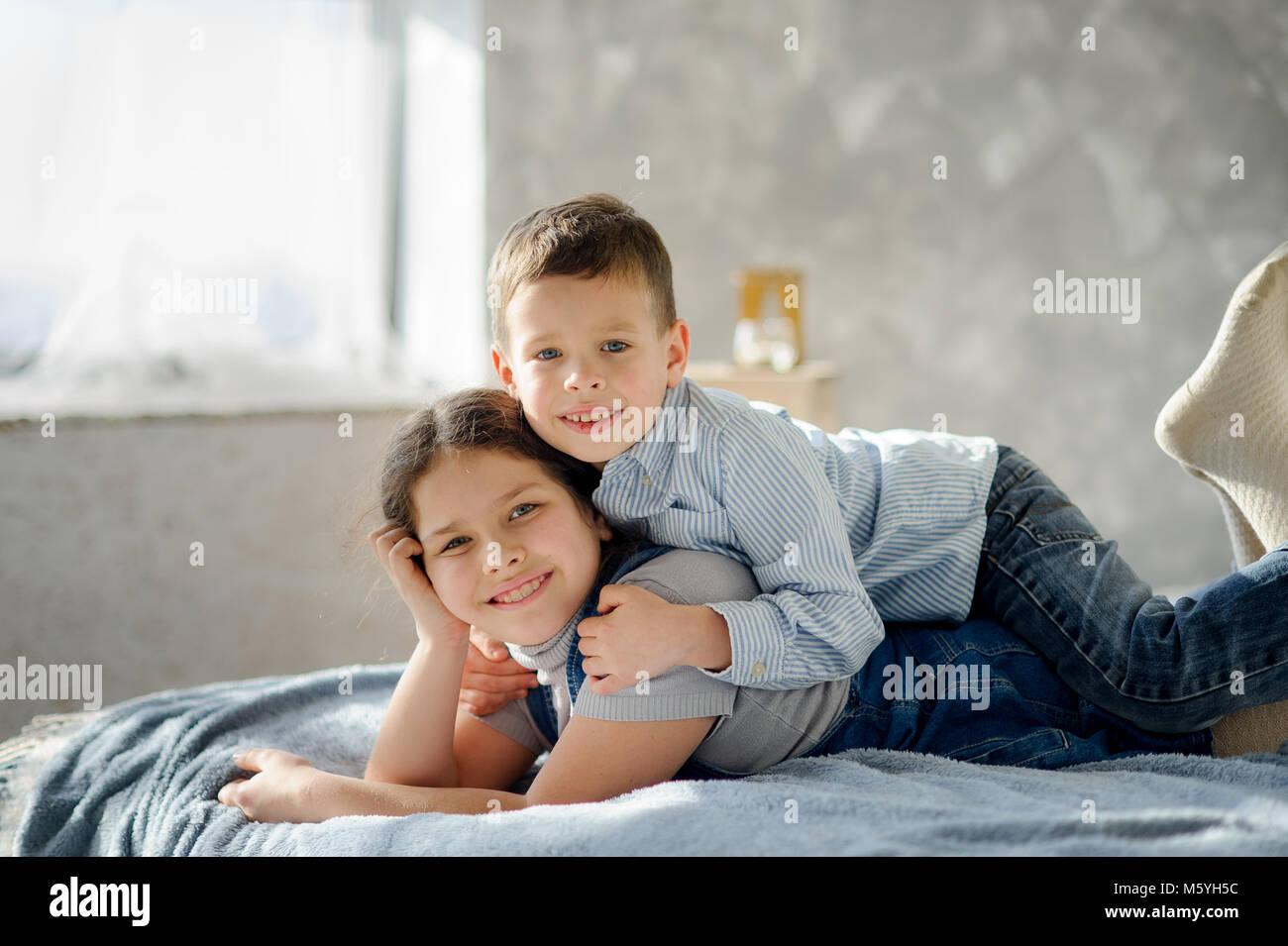 https www alamyimages fr photo image deux enfants le garcon et la fille se coucher sur un lit le jeune frere embrasse ainee pour les epaules les enfants ont une bonne humeur 175783144 html