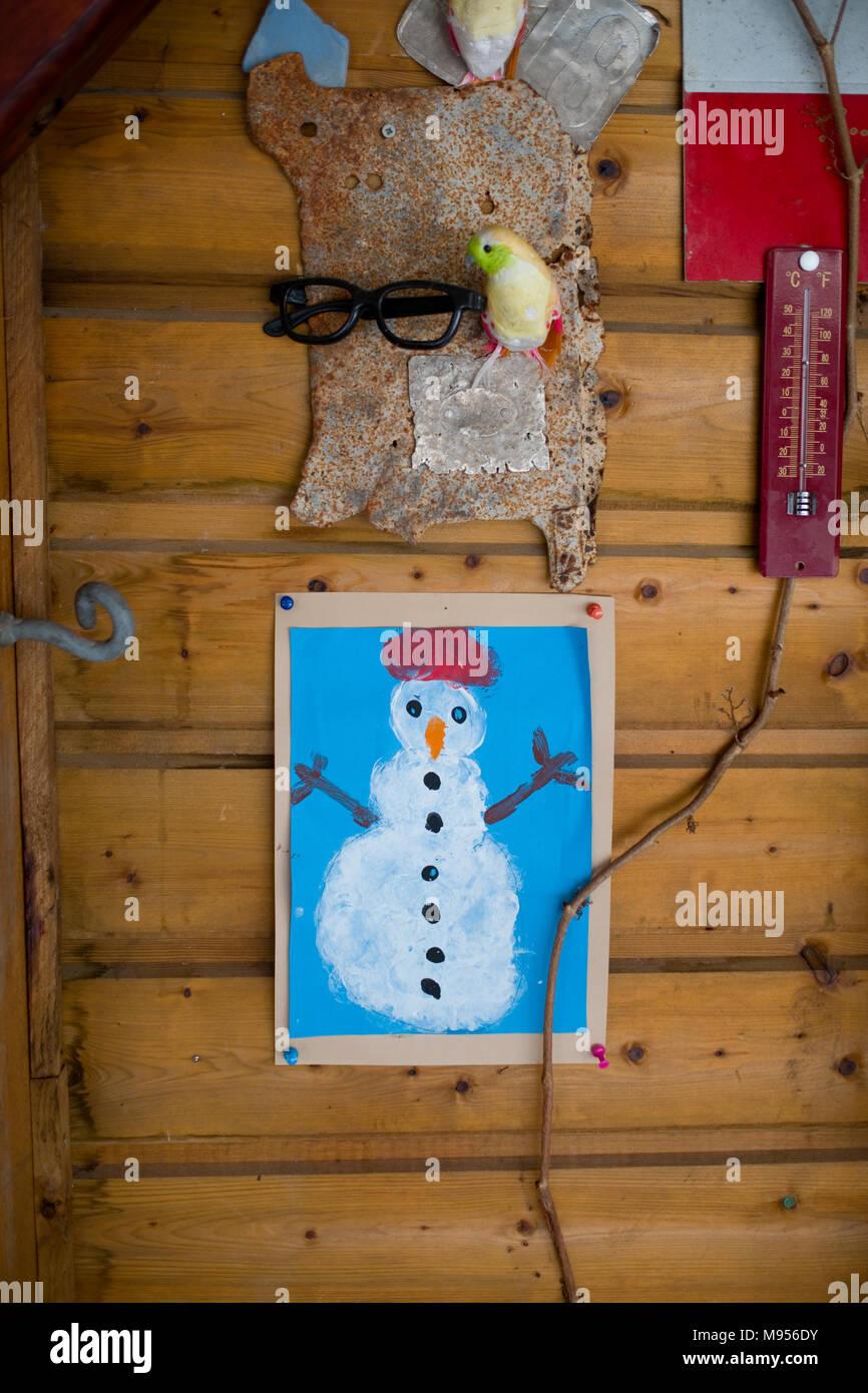 https www alamyimages fr peinture d un enfant d un bonhomme est accrochee a un mur en bois d un chalet a cote d une serie de d autres objets trouves y compris un thermometre image177750439 html