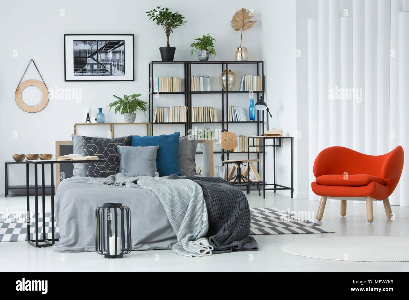 https www alamyimages fr fauteuil orange a cote du lit dans la chambre grise avec interieur poster sur mur blanc au dessus de bookshelf image181279367 html