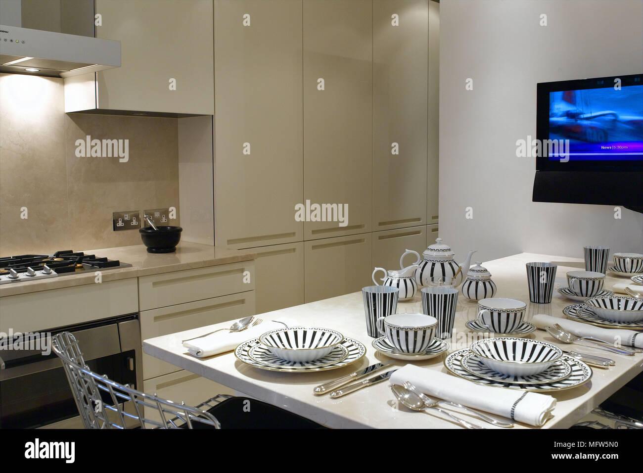 https www alamyimages fr une cuisine moderne avec des unites de cuisine beige face a une table de cuisine avec des couverts et une grande television ecran plat en encastre dans le mur image181876828 html
