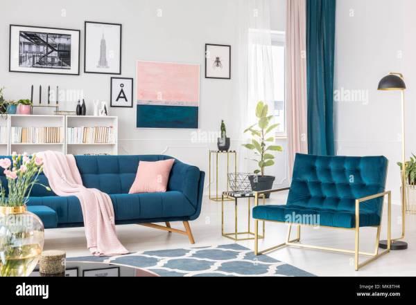 Fauteuil bleu à côté du canapé avec coussin rose dans un ...