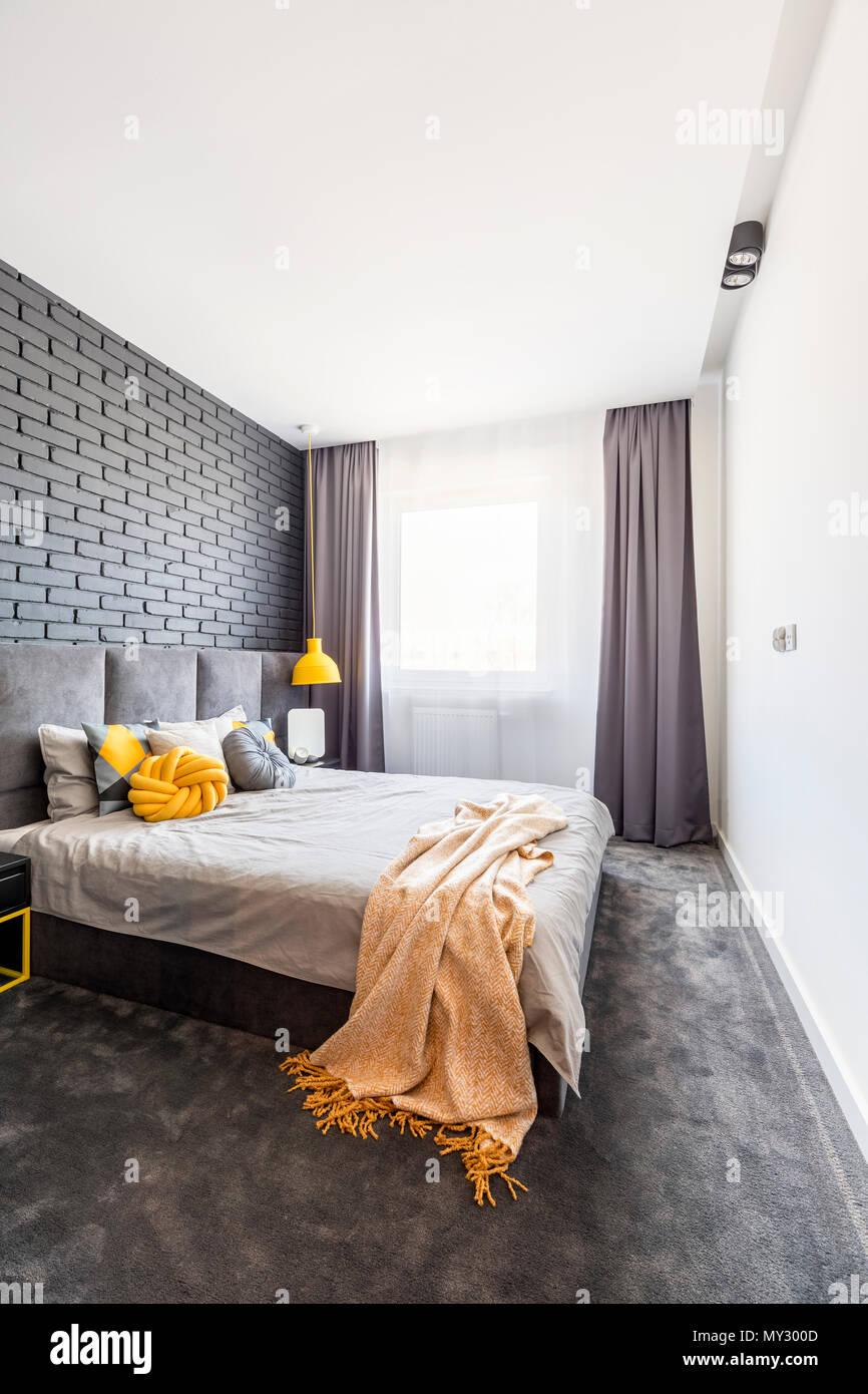 https www alamyimages fr couverture jaune sur lit dans chambre gris interieur avec mur de briques et de rideaux de fenetre a image188765261 html