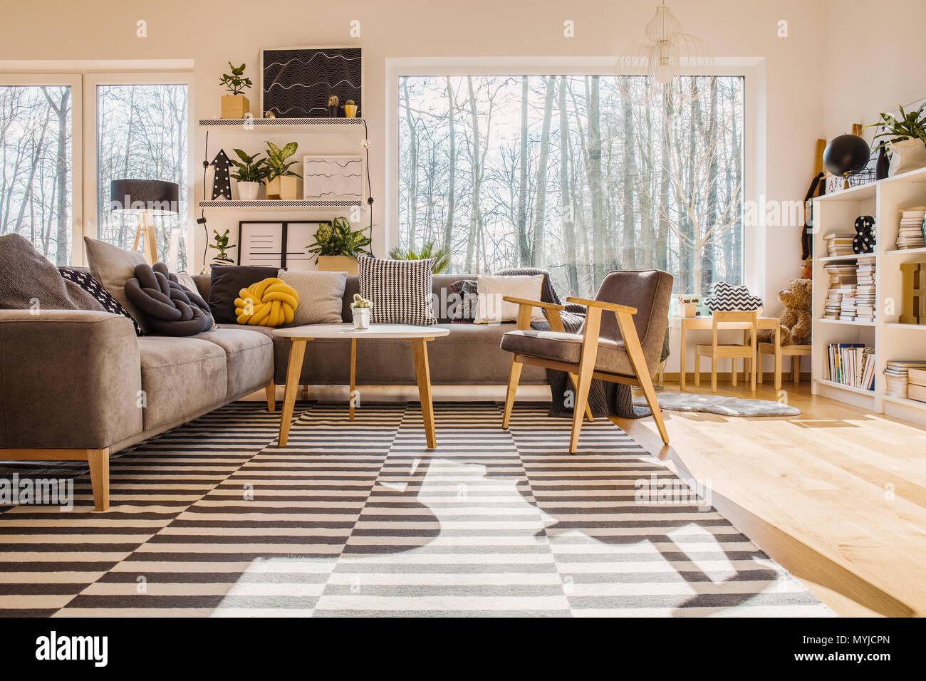 https www alamyimages fr l angle faible de l interieur chaleureux salon lumineux avec un fauteuil a cote de la table en bois canape d angle image189104573 html