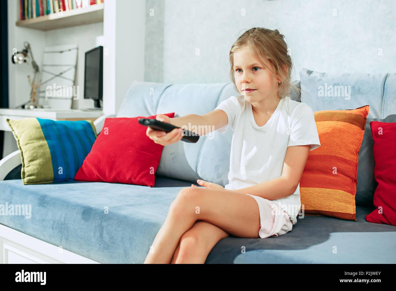 https www alamyimages fr peu casual girl regarder la tv a la maison femme enfant assis sur un canape avec tv satellite et de commutation a distance image208168883 html