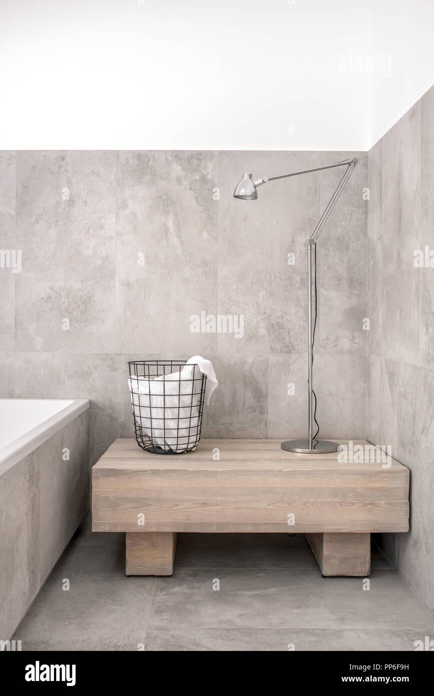 https www alamyimages fr quartier branche de salle de bains moderne avec sol carrele blanc et de murs gris il y a une baignoire en bois avec un stand metal black panier avec une serviette et une lampe d argent image220190589 html