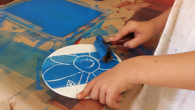Child uses blue paint during an artsREACH printmaking workshop