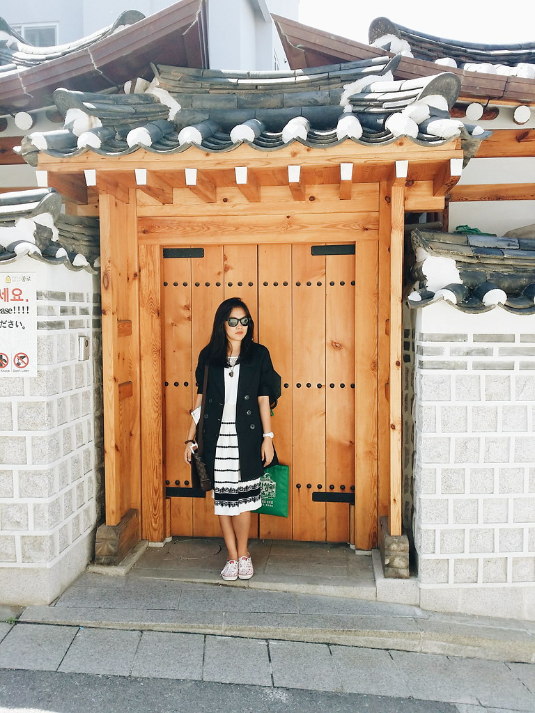 A girl standing in front of a big door of a hanok in Bukchon Hanok Village