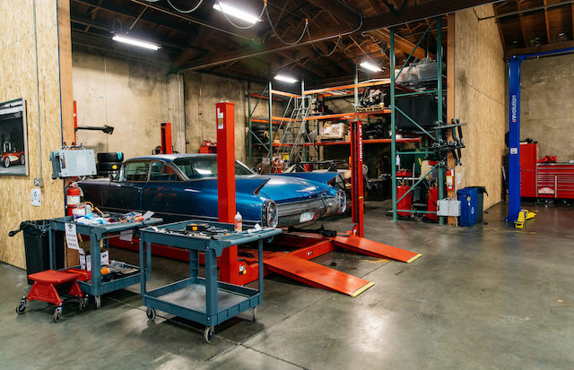 Auto body shop with vintage car on a lift