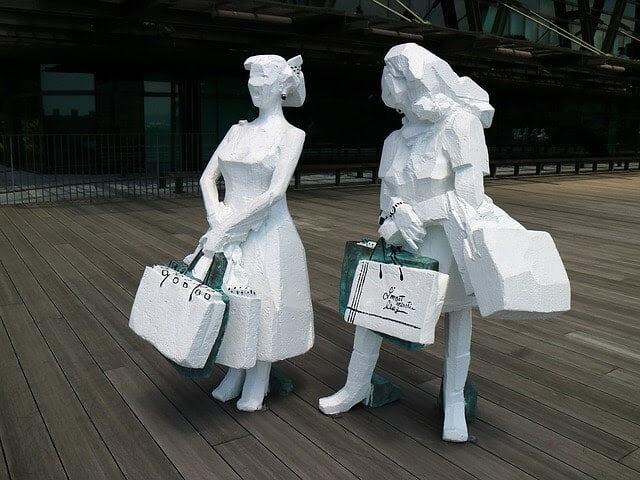 Small white statues that resemble women shopping