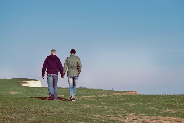 Two men holding hands as they walk outdoors.