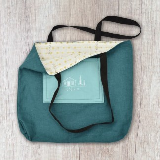 tote bag: deep teal textured solid exterior and white with gold arrows print interior