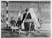 A policewoman helps schoolchildren across the road in 1951.