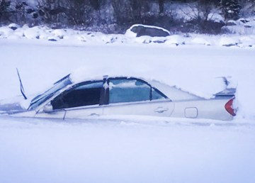 A vehicle is shown half-buried under ice in an image tweeted by the NWT's Department of Infrastructure