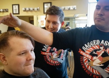 Ollie inspects Wheeler's progress during a hair styling contest