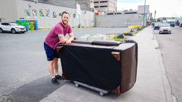 Cabin Radio general manager Andrew Goodwin escorts a sofa from Dan's Place to the radio station in September 2017