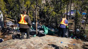Common Ground workers clear garbage from a Yellowknife trail