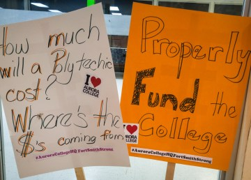 Signs brought to a public meeting over Aurora College's future by Fort Smith residents