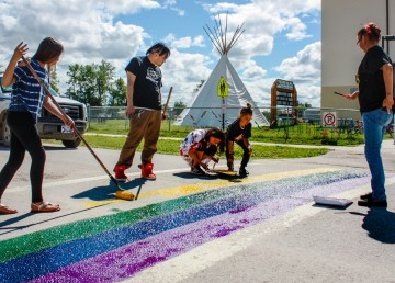 Students paint a rainbow crosswalk in front of Fort Smith's elementary school