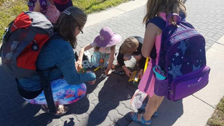 Campers at Natasha McCagg's yoga and nature camp inspect a bug