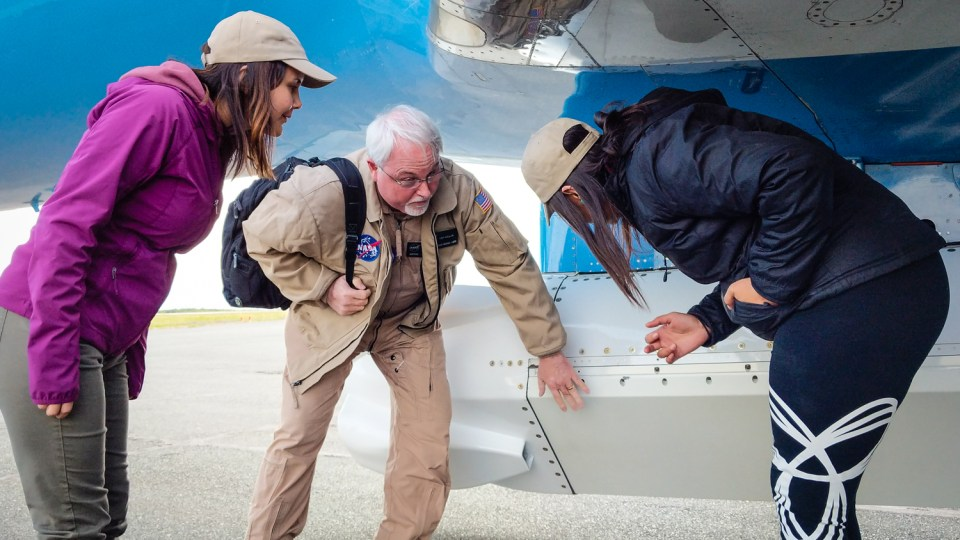 NASA's Tim Miller explains a feature of the team's radar pod to Joanne Speakman and Mandy Bayha