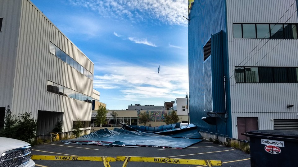 Siding lies crumpled at the foot of Yellowknife's Bellanca building