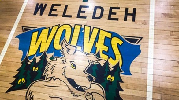 An image of the Weledeh Wolves logo on the school's gym floor, included in a presentation advocating for the school's name to change