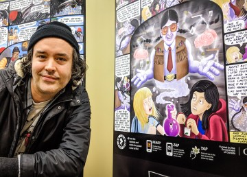 Cody Fennell, the artist behind a new NWT youth cannabis education campaign, poses with posters featuring his work