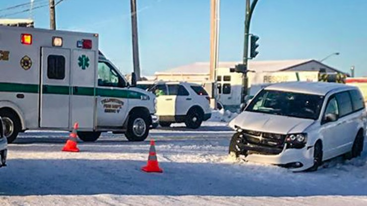 Emergency vehicles and a damaged car are seen on Yellowknife's Old Airport Road on January 28, 2019