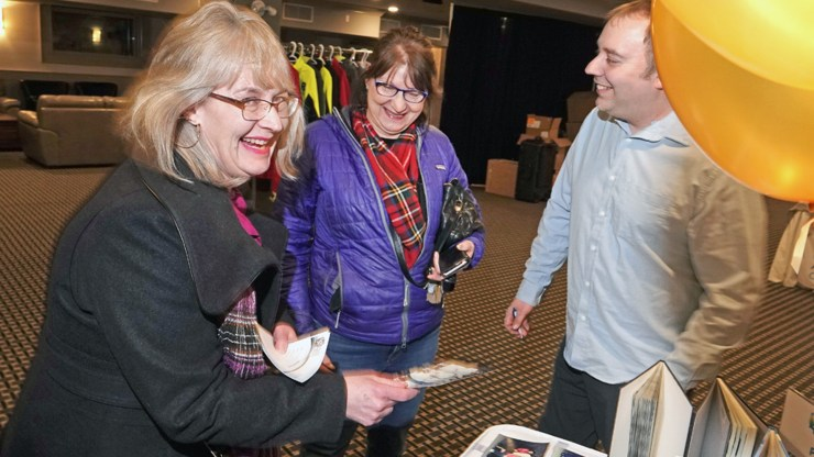 Aurora College alumni Lori Dashney, a nurse, Vivienne McQueen, left, a social worker, share a laugh over old class photos from their days at the school. College marketing and communications officer Jeff Turner shares in the moment.